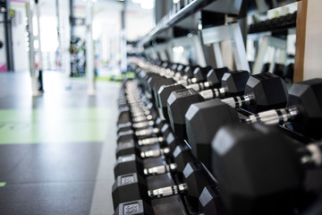 Keuken foto achterwand Fitness Closeup view of a rack of black dumbbells in a gym