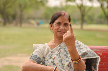 Fotorollo Affe A Senior Indian woman citizen sitting on the red bench in a park showing their inked finger after casting their vote in assembly elections in Delhi, India - world's largest democracy. Focus on finger