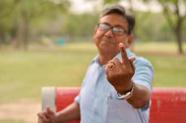 Foto auf Acrylglas Affe Portrait of a Senior Indian retired male sitting on the red bench in a park and showing his inked finger after casting their vote in Indian assembly elections