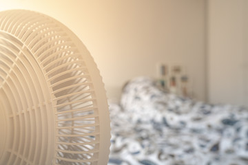Person sleeping in bed with a fan blowing on hot summer day