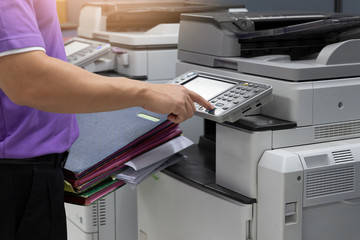 Bussinessman using copier machine to copy heap of paperwork in office. Wall mural