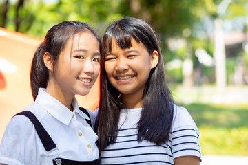 toothy smiling face of two asian teenager standing outdoor