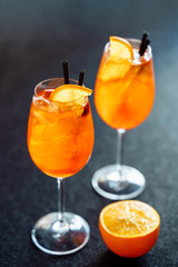 Aperol Spritz Sweet Cocktail Drink with Orange Ice. Bar Wine Aperitif Liqueur with Gin and Prosecco on Black Background. Cold Mixed Alcohol Beverage for Italian Nightclub. Spritzer Vertical Commercial