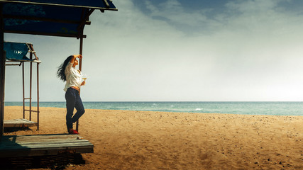 Beautiful Young Girl With a Glass Of Wine Stands On The Beach And Enjoys The Beautiful Scenery. Vacation health happiness concept