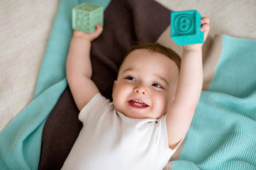 One-year-old boy playing on the bed in the bedroom. Next there is striped plaid. The boy smiles sincerely and plays with cubes.