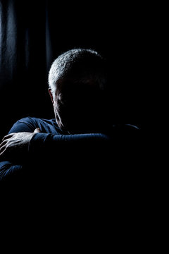 A man is sitting alone in a dark room. Concept loneliness.
