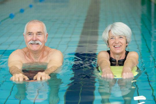elderly couple doing swimming drill exercises