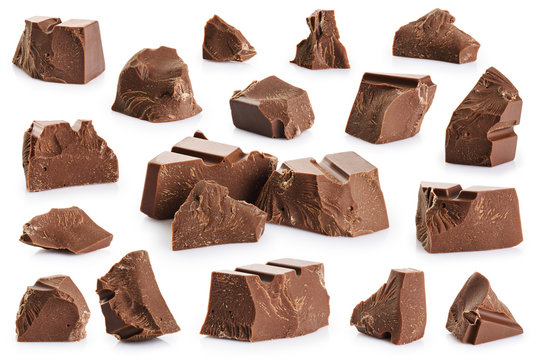 Pieces of milk chocolate isolated on white background.