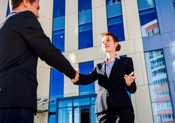 Professional business woman and man in formal suit shaking hands outdoors.
