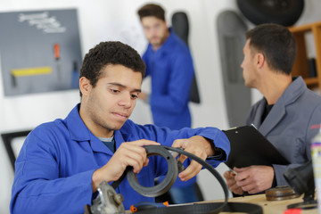 man with apprentices holding bearing