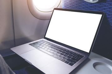 Mockup image of laptop computer with blank white desktop screen in the cabin