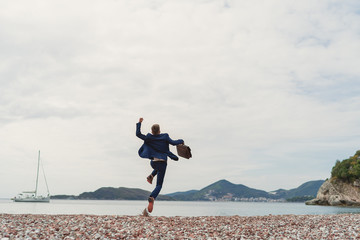Businessman jumping into the sea holding in hand briefcase. Back view