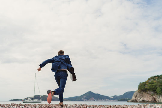 Businessman running to the sea holding in hand briefcase. Back view