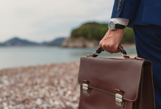 Businessman holding in hand briefcase on background the beach