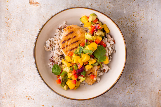 Grilled chicken with mango avocado salsa and rice in a light bowl, top view