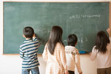 黒板にアルファベットを書く小学生
