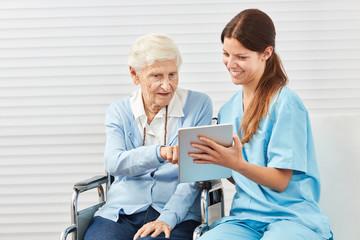 Wall Mural - Neugierige Seniorin im Rollstuhl mit Tablet PC