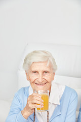 Wall Mural - Seniorin trinkt ein Glas mit Orangensaft