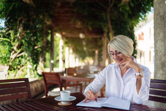 Happy senior woman writing to notebook or diary at a cafe