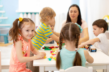 Cute woman and adorable kids playing educational toys at kindergarten or nursery room