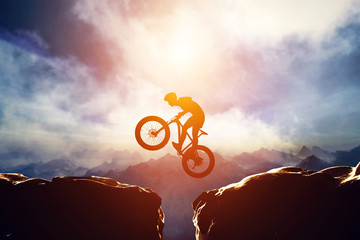 Man jumping with bike between two high mountains