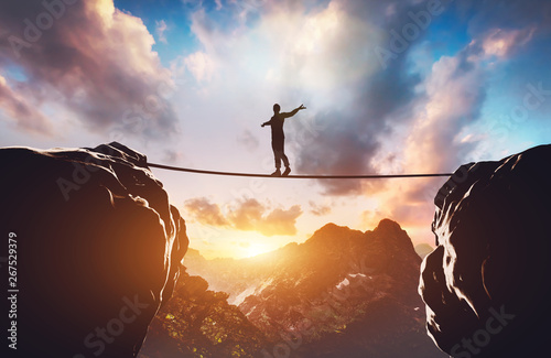 Wall mural Man walking on rope between two high mountains