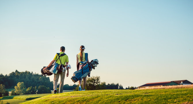 Happy couple carrying stand bags towards the golf course in a sunny day