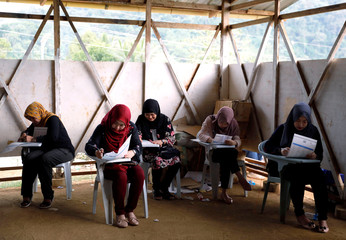 Voters fill out their ballots in a makeshift polling precint for internally displaced people in Marawi City