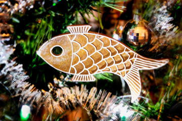 Sweet gingerbread in fish shape hanging on an ornate Christmas tree. Close-up of handmade aromatic cookie on blurry background of green needles, Xmas garlands and lights. Beautiful holiday atmosphere.