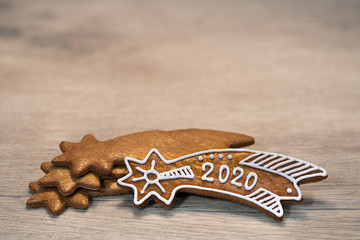 Ornate New Year Bethlehem stars. Still life on wood background. Handmade baked Xmas gingerbread cookie decorated by sugar icing, laid on stacked golden sweets. For good luck in 2020. Selective focus.