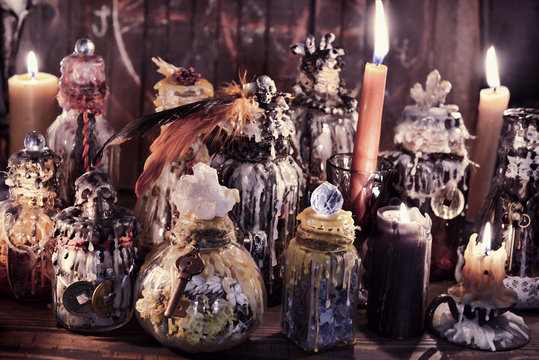 Witch bottles and candles in magic candlelight on the table