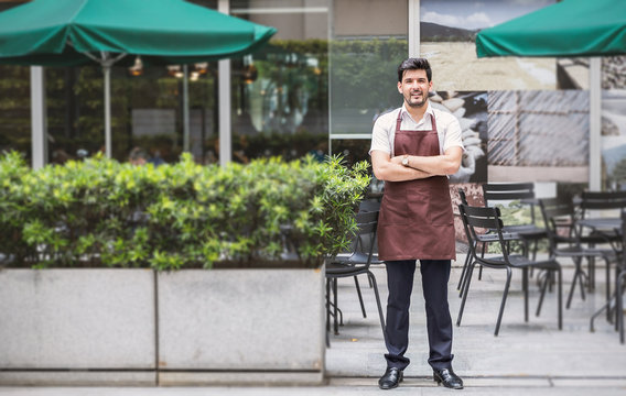 Startup successful small business owner man walking in his coffee shop or restaurant. Portrait of young caucasian man successful barista cafe owner