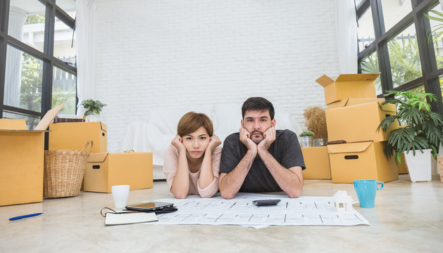 Couple Asian woman caucasian man with boxes planing for decorate with pile of blue print plan paper boxes. Moving house just married diversity interracial couple. Stressful financial problem concept.