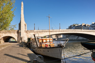 Paris in Spring, saailing boat on river Seine by the bridge de la Tournelle with statue of Saint Genevieve