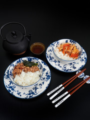 Asian style chicken, with rice, in white and blue bowls, on dark brown background