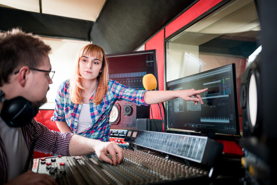 Music engineer and musician working together in recording studio using mixing desk