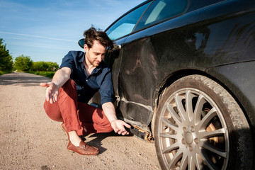 Angry man next to a car with damage on the left side and rotten sill on the bottom