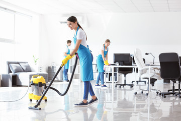 Team of janitors cleaning office
