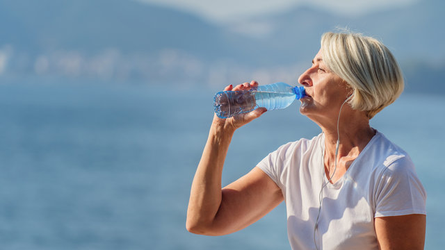 Mature woman drinking water after jogging on background the sea and blue sky