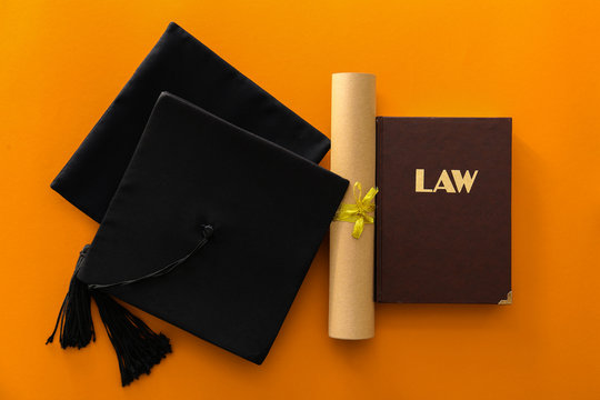 Mortar board, diploma and book on color background. Concept of law school graduation