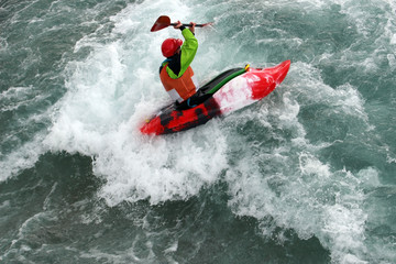 An experienced canoeist paddles on white water rapids.