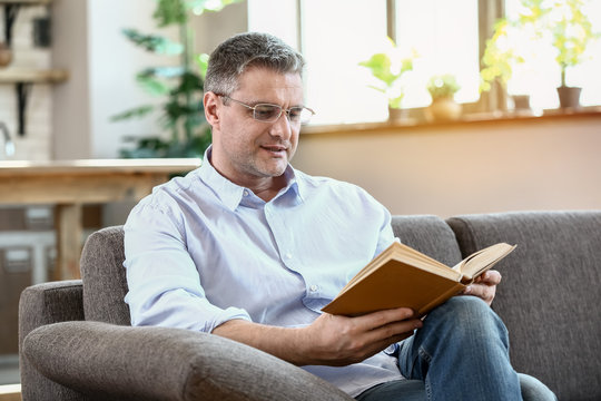 Handsome mature man reading book at home