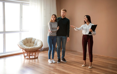 Real estate agent showing young couple a new house