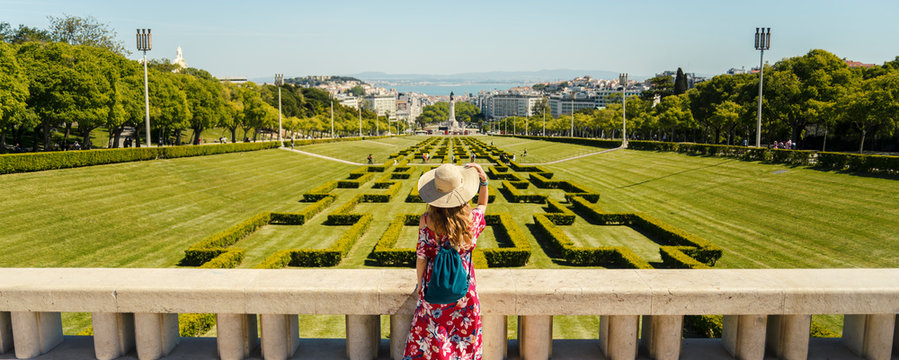 Young blonde woman wearing red generic sundress and a hat looking at cityscape view of Lisbon, capital city of Portugal