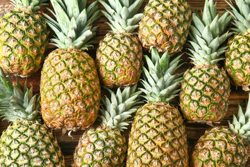 Many ripe pineapples as background