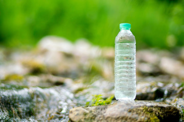 Plastic bottle with fresh cool water on nature background.