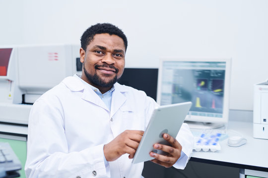 Content confident young black medical expert with beard and mustache sitting at desk with modern computer and using digital tablet in laboratory
