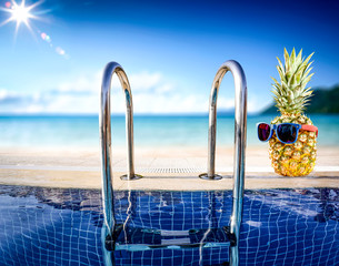 Fresh fruit of pineapple with swimming pool background. Summer sunny day and landscape of beach with ocean.
