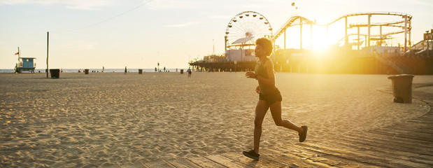 athletic african american woman jogging on boardwalk at sunset