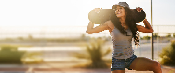 Smiling woman holding skateboard during sunse in panoramic composition